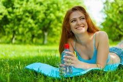 Meisje met fles water op gras royalty-vrije stock afbeeldingen