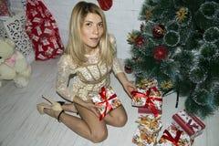 Meisje met giftdozen dichtbij Kerstmisboom Stock Afbeelding