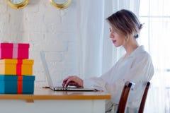 Meisje met giftdozen en laptop computer royalty-vrije stock afbeelding