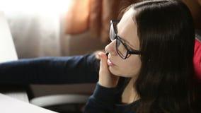 Meisje met glazen die op de telefoon spreken terwijl stock footage