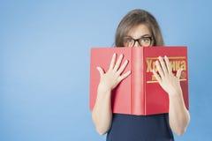 Meisje met glazen die van achter een groot boek piepen Stock Fotografie