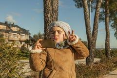 Meisje met grappig kusgezicht en grijze bonnet die een selfie nemen royalty-vrije stock afbeeldingen