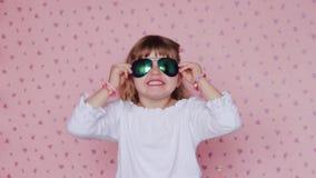 Meisje met grote zonnebril, makend gezichten en hebbend pret; kinderen en positieve emoties stock footage