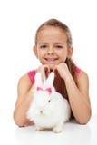 Meisje met haar aanbiddelijk wit konijn Stock Foto