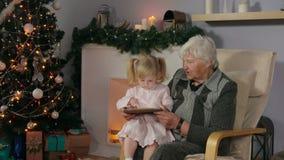 Meisje met haar grootmoeder die de tabletfoto's bekijken stock footage