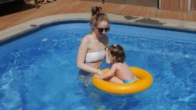 Meisje met haar mamma met opblaasbare cirkel in zwembad stock video