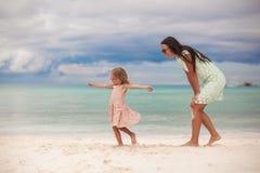 Meisje met haar moeder die bij witte zandig dansen Stock Foto