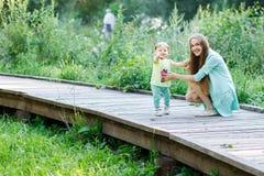 Meisje met haar moeder op houten brug in park Royalty-vrije Stock Foto's