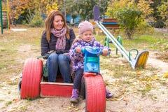 meisje met haar moederzitting bij children& x27; s eigengemaakte motorfiets in de werf stock afbeelding