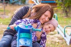 meisje met haar moederzitting bij children& x27; s eigengemaakte motorfiets in de werf stock foto's