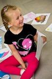 Meisje met haar tekeningen op de vloer Stock Afbeelding