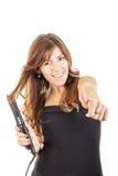 Meisje met hairstraightener die haar haar krullend maken stock foto