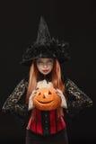 Meisje met Halloween-pompoen op zwarte achtergrond Stock Afbeeldingen