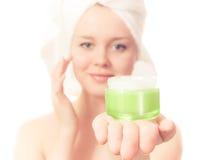 meisje met handdoek op haar hoofd en room. stock afbeelding
