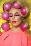 Meisje met heldere make-up en haarballen op gele achtergrond stock afbeelding