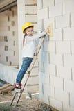 Meisje met helm die bij de bouw werken Stock Foto