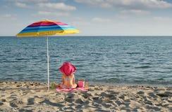 Meisje met het zitten onder zonnescherm op strand Royalty-vrije Stock Foto's