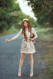 Meisje met hoed en rugzak die op de weg liften Royalty-vrije Stock Fotografie