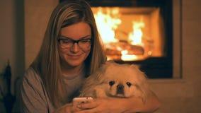 Meisje met hond die telefoon met behulp van dichtbij de open haard stock videobeelden
