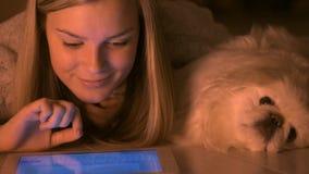 Meisje met hond die telefoon met behulp van dichtbij de open haard stock video