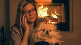 Meisje met hond sprekende telefoon dichtbij de open haard stock footage