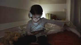Meisje met hoofdtelefoons die terwijl het bekijken de tablet dansen stock videobeelden