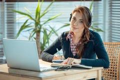 Meisje met hoofdtelefoons en laptop Stock Afbeelding