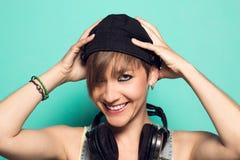 Meisje met hoofdtelefoons en positieve houding Vrouw met het glimlachen van muziekhoofdtelefoons stock afbeelding
