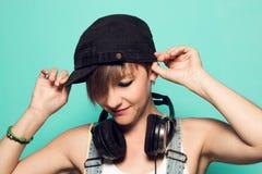 Meisje met hoofdtelefoons en positieve houding Vrouw met het glimlachen van muziekhoofdtelefoons royalty-vrije stock afbeelding
