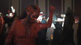 Meisje met hoornen als dans van het duivelskarakter in menigte bij de partij van Halloween van de nachtclub stock videobeelden
