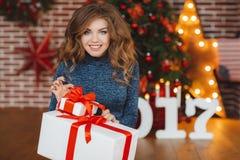 Meisje met Kerstmisgift dichtbij mooie geklede Kerstboom Royalty-vrije Stock Foto