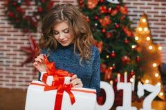 Meisje met Kerstmisgift dichtbij mooie geklede Kerstboom Royalty-vrije Stock Afbeelding