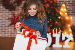 Meisje met Kerstmisgift dichtbij mooie geklede Kerstboom Royalty-vrije Stock Fotografie