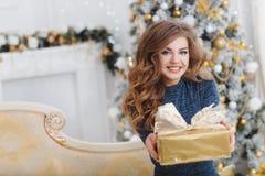Meisje met Kerstmisgift dichtbij mooie geklede Kerstboom Stock Afbeeldingen