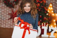 Meisje met Kerstmisgift dichtbij mooie geklede Kerstboom Royalty-vrije Stock Foto's
