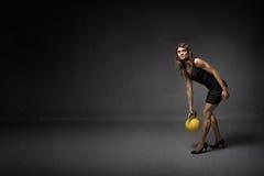 Meisje met kettlebell en hoge hielen stock fotografie