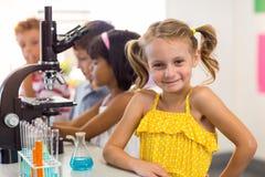 Meisje met klasgenoten in laboratorium royalty-vrije stock afbeelding