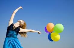 Meisje met kleurenballons bij blauwe hemelachtergrond. Royalty-vrije Stock Afbeelding
