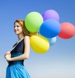 Meisje met kleurenballons bij blauwe hemelachtergrond. Stock Afbeeldingen