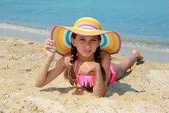 Meisje met kleurrijke hoed op het strand stock fotografie