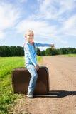 Meisje met koffer die zich over weg bevinden Stock Afbeelding