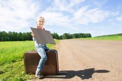 Meisje met koffer die zich over weg bevinden Stock Fotografie