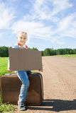 Meisje met koffer die zich over weg bevinden Stock Foto's