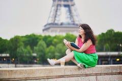 Meisje met koffie gaan lezend een boek dichtbij de toren van Eiffel royalty-vrije stock foto's