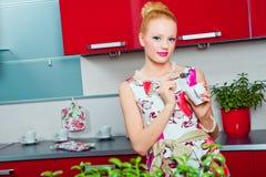 Meisje met kop van koffie in binnenland van keuken Stock Fotografie
