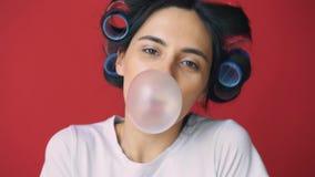 Meisje met krulspelden op haar hoofd en gom blazende bel op rode achtergrond stock videobeelden