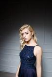 Meisje met lang blond haar in donkerblauwe kleding royalty-vrije stock afbeeldingen