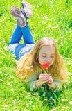 Meisje met lang haar die op grassplot, grasachtergrond liggen Het kind geniet van geur van tulp terwijl het liggen bij weide De l stock foto