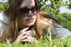 Meisje met lang haar in een opheldering onder het gras royalty-vrije stock foto's