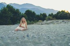 Meisje met lange blonde haarzitting alleen door het overzees Royalty-vrije Stock Foto's